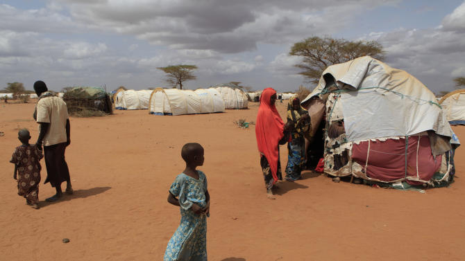 Recently-arrived Somali refugees walk amongst makeshift shelters and United Nations tents in an informal settlement on the outskirts of Dagahaley Camp, outside Dadaab, Kenya, Sunday, July 10, 2011. The United Nations High Commissioner for Refugees estimates 1300 new refugees fleeing drought and hunger in Somalia are arriving daily in the Dadaab area of northern Kenya. (AP Photo/Rebecca Blackwell)