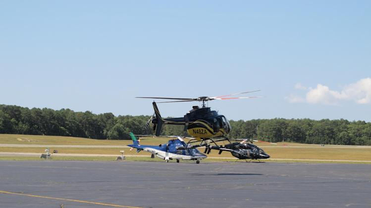In this Aug. 20, 2014 photo, a helicopter tales off in front of two other choppers at East Hampton Town Airport. Residents across eastern Long Island are complaining about the noise generated from jets, helicopters and other aircraft that land at the small municipal airport, which is situated in the heart of the summer playground for the rich and famous. (AP Photo/Frank Eltman)