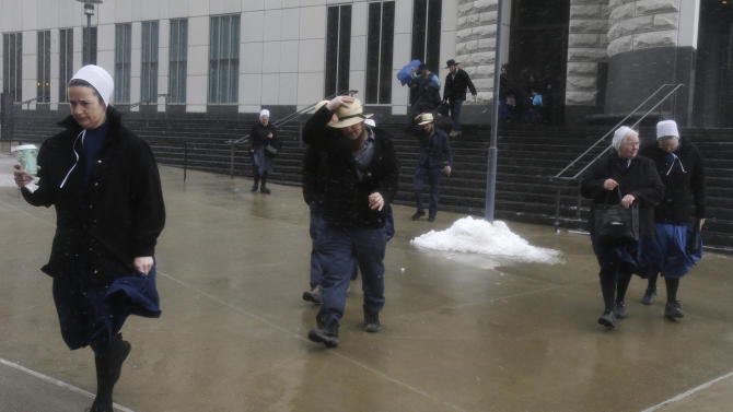Amish men and women leave the U.S. Federal Courthouse Friday, Feb. 8, 2013, in Cleveland.  Sam Mullet Sr., 67, the ringleader in a series of unusual hair- and beard-cutting attacks on fellow Amish religious followers in the U.S. was sentenced Friday to 15 years in prison, and 15 family members received sentences of one year to seven years. The defendants were charged with a hate crime because prosecutors believe religious differences brought about the attacks.  (AP Photo/Tony Dejak)