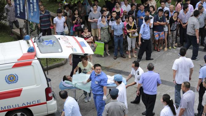 Medical personnel transport a victim at a hospital after an explosion at a factory in Kunshan