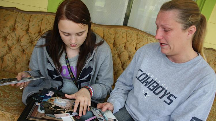 "FILE - In this April 17, 2012, file photo, Kenneth Weishuhn's sister, Kayla Weishuhn, 16, and his mother, Jeannie Chambers, look at photos of Kenneth, 14, who committed suicide April 15 at their home Primghar, Iowa. Chambers said she knew her son was being harassed but that she and the rest of the family didn't realize the extent of the bullying. The Sioux City Journal's front-page opinion piece on its Sunday, April 22 edition calls on the community to be pro-active in stopping bullying and urges members to learn more about the problem by seeing the acclaimed new film, ""Bully,"" which documents the harassment of Sioux City middle school student. It notes that while many students are targeted for being gay, ""we have learned a bully needs no reason to strike."" (AP Photo/Sioux City Journal, Laura Wehde)"