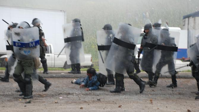 A wounded man lies amidst military police dressed in riot gear during clashes with peasants protesting against the cost of electricity in Santa Catarina Ixtahuacan, west of Guatemala City on Thursday Oct. 4, 2012. At least two people have been killed and dozen others seriously wounded in the confrontation between protesters and security forces. (AP Photo)