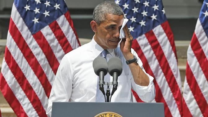 President Barack Obama wipes perspiration from his face as he speaks about climate change, Tuesday, June 25, 2013, at Georgetown University in Washington. The president is proposing sweeping steps to limit heat-trapping pollution from coal-fired power plants and to boost renewable energy production on federal property, resorting to his executive powers to tackle climate change and sidestepping the partisan gridlock in Congress. (AP Photo/Charles Dharapak)