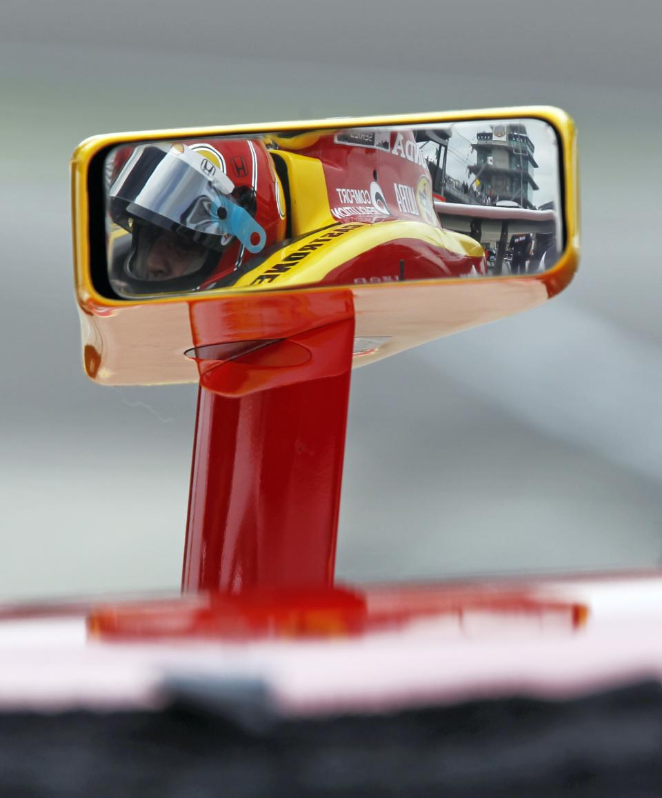 Helio Castroneves, of Brazil, is reflected in one his car's mirrors during practice for the Indianapolis 500 auto race at the Indianapolis Motor Speedway in Indianapolis, Saturday, May 14, 2011. (AP Photo/Darron Cummings)