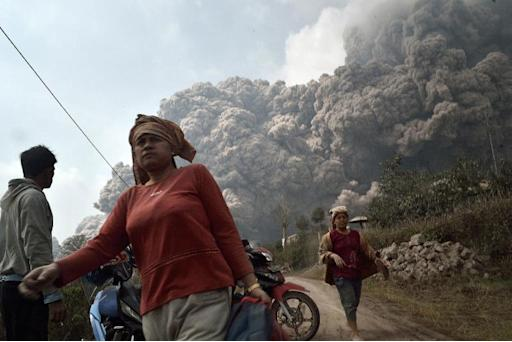 Residents run to escape from hot volcanic ash clouds engulfing villages in Karo district during the eruption of Mount Sinabung in Indonesia's Sumatra island on February 1, 2014