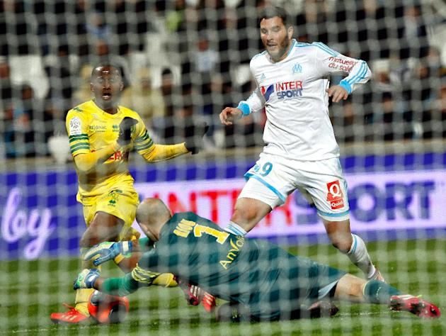 Marseille's French forward Andre-Pierre Gignac, right, challenges for the ball with Nantes' French goalkeeper Remy Riou, centre and Nantes' Venezuelan defender Oswaldo Vizcarrondo, during