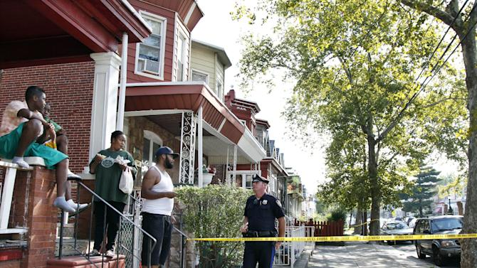 "A police officer talks to neighbors near 1415 Kaighn Ave., in Camden, N.J., Wednesday, Aug. 22, 2012.  Police say a New Jersey mother apparently decapitated her 2-year-old boy and put his head in the freezer of their home before she fatally stabbed herself. Chevonne Thomas, 33, called 911 just after midnight to say something had happened to her child and it ""sounded like she had done it,"" said Jason Laughlin, a spokesman for the county prosecutor's office. Officers found Zahree Thomas' body on the first floor of the Camden home and the boy's head in the freezer. The mother stabbed herself in the neck with a kitchen knife and died, Laughlin said. (Photo/Mel Evans)"