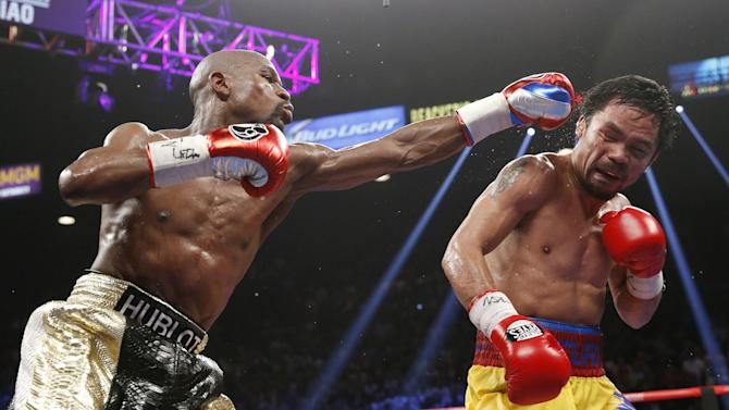 FILE - In this May 2, 2015 file photo, Floyd Mayweather Jr., left, hits Manny Pacquiao, from the Philippines, during their welterweight title fight in Las Vegas. The broadcast of fight was marred by technical snafus and got sucker punched by Internet streamers, exposing the industry's vulnerabilities. (AP Photo/John Locher, File)