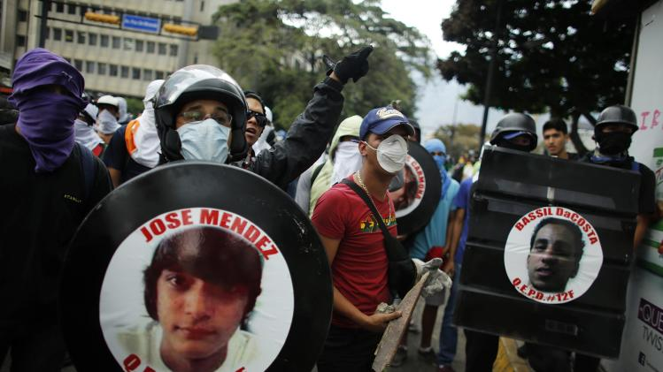Anti-government protesters hold photographs of victims of violence during a protest at Altamira square in Caracas
