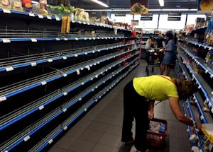 Shoppers stand in an aisle with empty shelves in a …