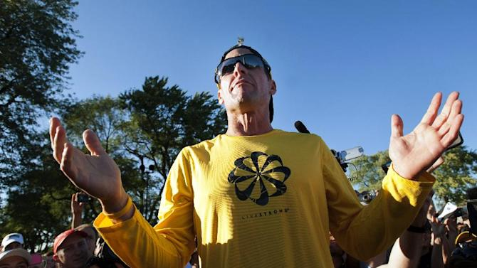 Lance Armstrong talks to supporters prior to a run, Wednesday, Aug. 29, 2012, on Mont Royal Park in Montreal. (AP Photo/The Canadian Press, Graham Hughes)