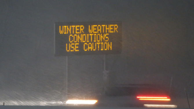 A vehicle travels past a warning sign on I-70 east of Topeka, Kan., Monday, Feb. 25, 2013.  Jayson Gosselin of the National Weather Service says parts of Colorado, Kansas and northern Missouri could get 10 to 12 inches of snow.  (AP Photo/Orlin Wagner)