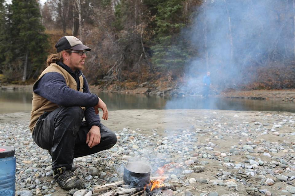 "In this 2012 photo released by National Geographic Channels and Brian Catalina Entertainment, Brent Sass sits by a camp fire in McCarthy, Alaska. Sass is among eight mushers or outdoor adventurers featured in the latest reality show set in Alaska. ""Ultimate Survival Alaska"" premieres Sunday on NatGeoTV. (AP Photo/Brian Catalina Entertainment, Kyle Wheeler)"