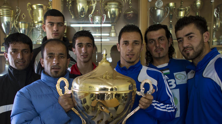 "In this Tuesday, Feb. 11, 2014 photo, Abu Hammad family members pose with the Yasser Arafat Cup at their club's trophy room in the West Bank village of Wadi al-Nees. Palestinian farmer Yousef Abu Hammad sired enough boys for a soccer team and the current roster of the Wadi al-Nees team includes six of Abu Hammad's sons, three grandsons and five other close relatives. Wadi al-Nees heads the West Bank's 12-team ""premier league,'' consistently defeating richer clubs and believe their strong family bonds are a secret to their success. (AP Photo/Dusan Vranic)"
