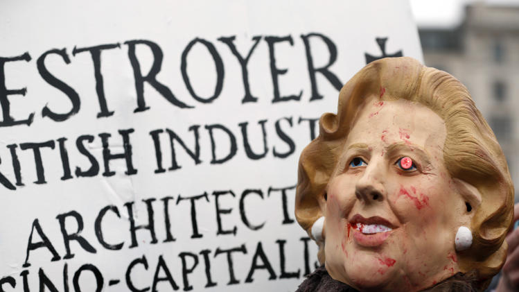 A protester wears a mask depicting former British Prime Minister Margaret Thatcher during a party to mark her death in central London's Trafalgar square, Saturday, April 13, 2013. Thatcher's most strident critics had long vowed to hold a gathering in central London on the Saturday following her passing, and the festivities were an indication of the depth of the hatred which some Britons still feel for their former leader. (AP Photo/Lefteris Pitarakis)