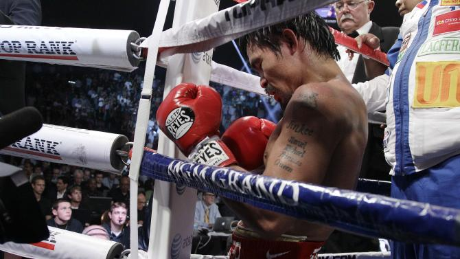 Manny Pacquiao, from the Philippines, kneels in his corner following his split decision loss to Timothy Bradley, from Palm Springs, Calif., in their WBO world welterweight title fight Saturday, June 9, 2012, in Las Vegas. (AP Photo/Julie Jacobson)