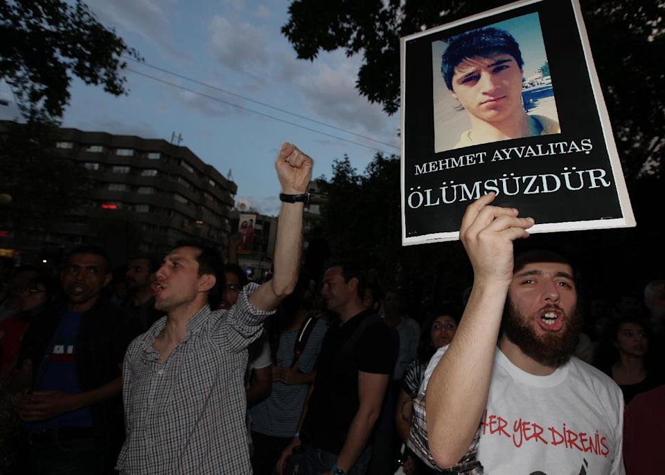 People hold posters of Mehmet Ayvalitas, one of five people killed during the protests as a group of Turkish protesters continue to sit in Kugulu Park in Ankara, Turkey, Thursday, June 13, 2013.(AP Photo/Burhan Ozbilici)