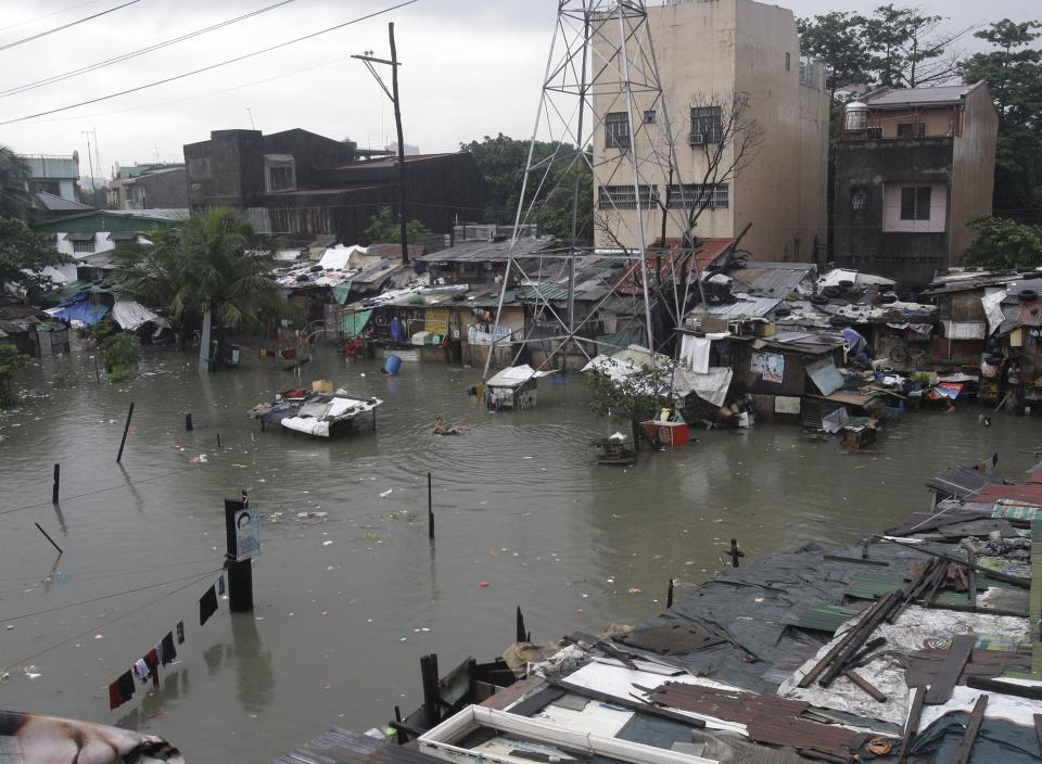A squatter area is seen submerged by flood water Tuesday, Aug. 2, 2001 in suburban Quezon City, north of Manila, Philippines. A powerful typhoon is blowing away from the northern Philippines after killing at least four people even though it did not make landfall. (AP Photo/Pat Roque)