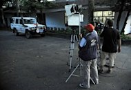 Staff of Colombian television channels set up their equipment outside the International Committee of the Red Cross (ICRC) headquarters in Florencia, Caqueta department, Colombia, on May 6. Leftist guerrillas in Colombia have asked for a &quot;debate&quot; over the role of the press in Colombia before they will free a French journalist captured last month