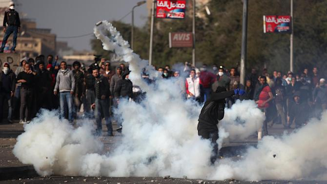 Egyptian protesters clash with riot police, unseen, near Tahrir Square, Cairo, Egypt,Tuesday, Jan. 29, 2013. Intense fighting for days around central Tahrir Square engulfed two landmark hotels and forced the U.S. Embassy to suspend public services on Tuesday. (AP Photo/Khalil Hamra)