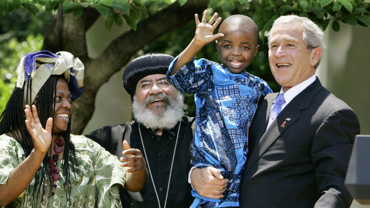 """FILE – In is May 30, 2007, file photo President Bush, right, hoists 4-year-old Baron Mosima Loyiso Tantoh, son of Manyongo Mosima """"Kuene"""" Tantoh of South Africa, left, who is HIV-positive, after speaking about his efforts to fight HIV/AIDS worldwide, in the Rose Garden of the White House in Washington. At center is Coptic Orthodox Church Bishop Paul Yowakim of Kenya. The decade-old law that transformed the battle against HIV/AIDS in developing countries is at a crossroads, the dream of future generations freed from epidemic running up against an era of economic recovery and harsh budget cuts. The President's Emergency Plan for AIDS Relief grew out of an unlikely partnership between Bush and lawmakers led by the Congressional Black Caucus, and has come to represent what Washington can do when it puts politics aside_and what America can do to make the world a better place. (AP Photo/J. Scott Applewhite, File)"""