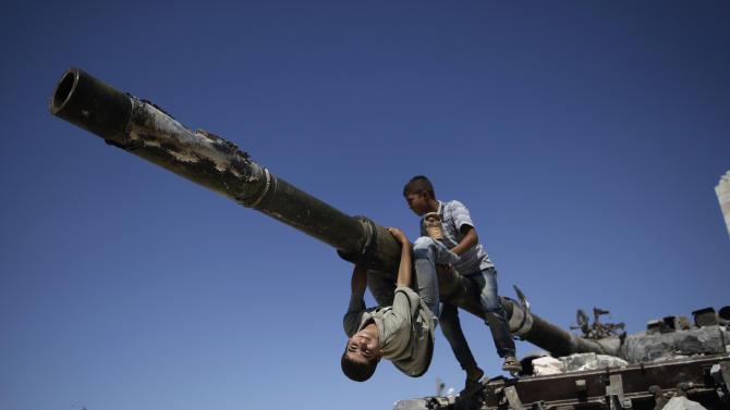 A  boy looks back while he and another boy play on a Syrian military tank, destroyed during fighting with the Rebels, in the Syrian town of Azaz, on the outskirts of Aleppo, Sunday, Sept. 2, 2012. (AP Photo/Muhammed Muheisen)