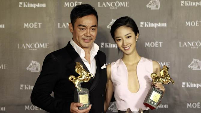 """Taiwanese actress Gwei Lun-Mei and Hong Kong actor Lau ChingWan hold their awards for Best Actress and Best Actor for the film """"GF * BF"""" and """"Life Without Principle"""" at the 49th Golden Horse Awards at the Luodong Cultural Working House in Yilan County, Taiwan, Saturday, Nov. 24, 2012. The Golden Horse awards are the Chinese-language film industry's biggest annual events. (AP Photo/Wally Santana)"""