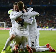 Real Madrid's Argentinian forward Gonzalo Higuain (L) celebrates next to Real Madrid's French defender Raphael Varane (R) and Real Madrid's defender Sergio Ramos after scoring during the UEFA Champions League quarter-final first leg football match Real Madrid vs Galatasaray on April 3, 2013 at Santiago Bernabeu stadium in Madrid. Real won 3-0