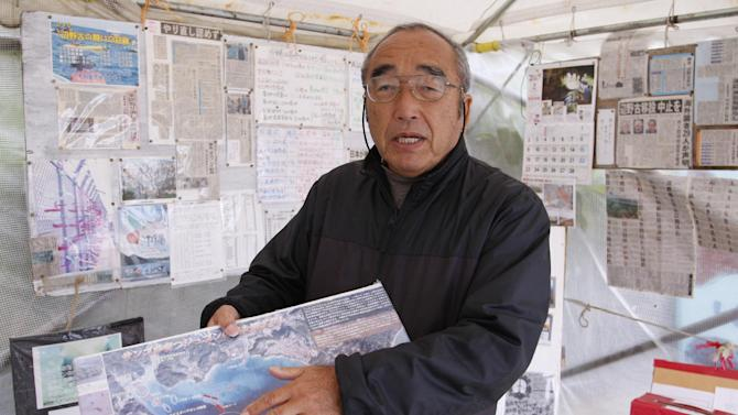 In this Thursday, Feb. 6, 2014 photo, Hiroshi Ashitomi, a retired welfare case worker, shows a protest map of Henoko where the U.S. and Japan agreed to relocate Marine Corps Air Station Futenma and plan to build an airstrip in the water dugongs and other sea creatures inhabit at his tent on the beach in Nago, Okinawa. For 10 years, He has been coming to the beach near his Okinawa home every day to sit. He loves nothing more than the sea around the island, the rare sightings of dugongs and sea turtles, the tan-colored sand and the crags out by the breakwater. Like many Okinawans, including leading politicians and media, Ashitomi opposes a plan to move the controversial Marine base to a less crowded part of the southern Japanese island. The proposed location for the new airstrip - Ashitomi's favorite beach - is the epicenter of the opposition. (AP Photo/Eric Talmadge)