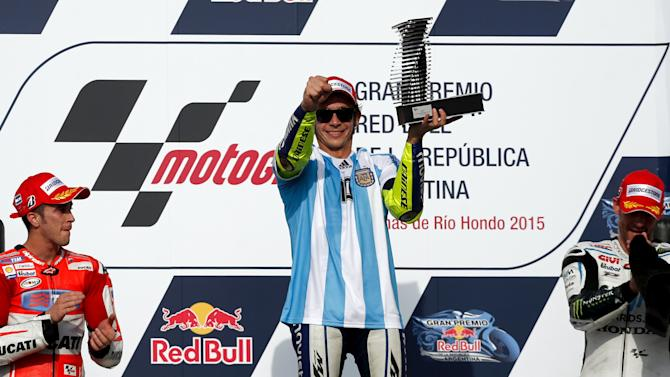Rossi of Italy lifts up the trophy as he celebrates at the podium next to Dovizioso and Crutchlow after he won Argentina's MotoGP Grand Prix in Termas de Rio Hondo