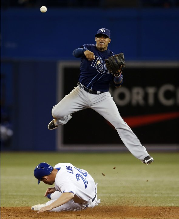 Rays  Escobar turns a double play over Blue Jays Lind during their MLB baseball game in Toronto