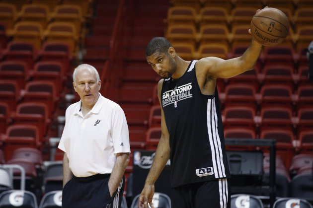 San Antonio Spurs Head Coach Greg Popovich talks with center Tim Duncan during a team practice ahead of Game 7 of the NBA Finals basketball playoff in Miami