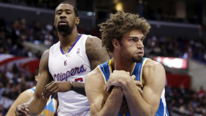 New Orleans Hornets center Robin Lopez, right, pulls in a rebound as Los Angeles Clippers' DeAndre Jordan watches during the first half of an NBA basketball game in Los Angeles, Wednesday, Dec. 19, 2012. (AP Photo/Chris Carlson)
