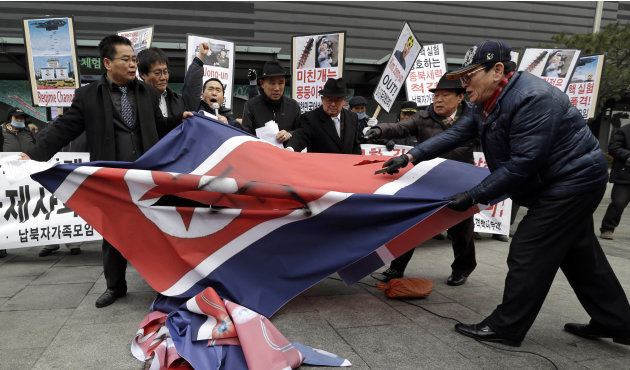South Korean protesters slit up a North Korean flag during an anti-North Korea rally in Seoul, South Korea, following a nuclear test conducted by North Korea Tuesday, Feb. 12, 2013. North Korea said i