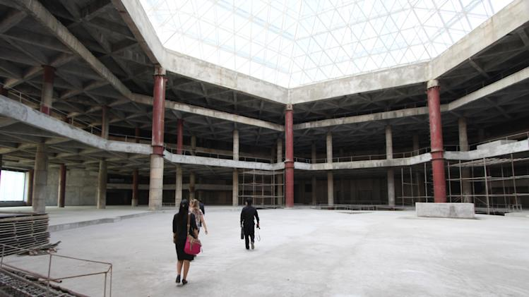 In this Sept. 23, 2012 photo released by Koryo Group, visitors tour the top floor of the 105-story Ryugyong Hotel in Pyongyang, North Korea. After years of standing unfinished, construction on the exterior of the massive hotel resumed three years ago but the hotel has not yet opened to the public. This photo taken by the Beijing-based Koryo Tours shows that the interior remains unfinished.   (AP Photo/Koryo Group) NO SALES, EDITORIAL USE ONLY