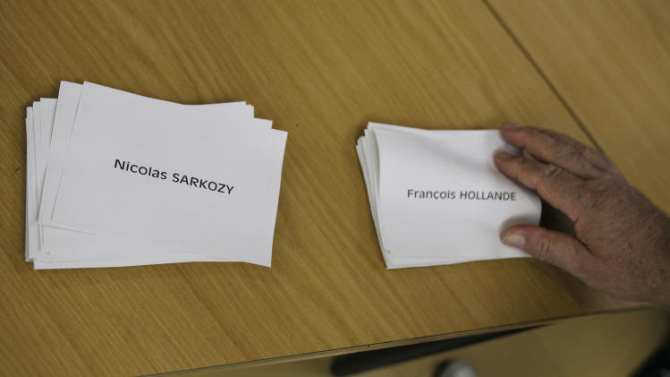A French citizen picks up a name card of a presidential candidate as he prepares to cast his vote at an overseas voting center inside the French Embassy in Makati, south of Manila, Philippines on Sunday, May 6, 2012. French citizens are choosing between Conservative President Nicolas Sarkozy and Socialist challenger Francois Hollande as they vote during the final round of presidential elections Sunday.(AP Photo/Aaron Favila)