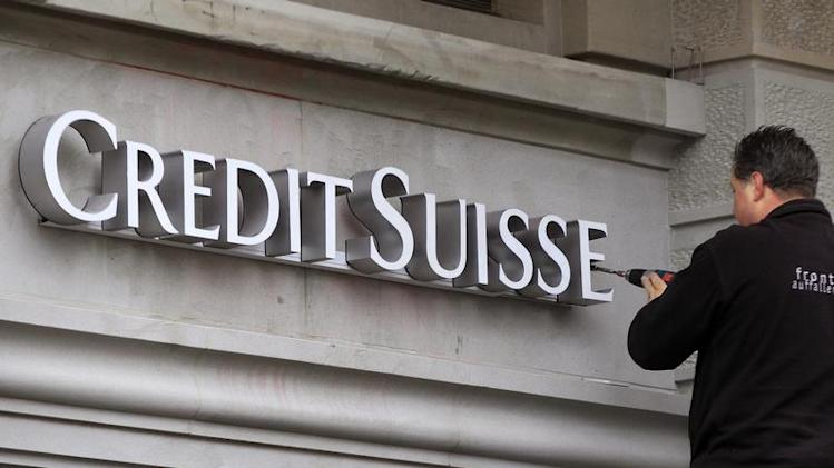 A worker uses a cordless screwdriver to fix the logo of Swiss bank Credit Suisse at a branch office in Zurich