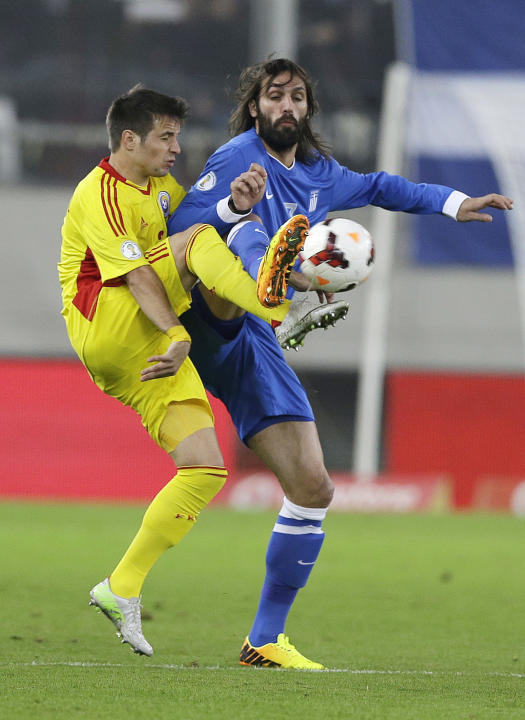 Greece's Giorgos Samaras, right, and Romania's Alexandru Matel in action during their World Cup qualifying playoff first leg soccer match at the Karaiskaki stadium in the port of Piraeus, near Athens,