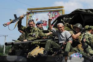 Pro-Russian militants wave as they drive past a checkpoint…