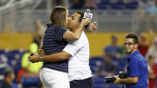 Cassandra Bersach and Juan Gallego kiss after after Bersach accepted a surprise marriage proposal from Gallego before a baseball game between the St. Louis Cardinals and the Miami Marlins on Tuesday, June 26, 2012, in Miami. Bersach had sung the national anthem. (AP Photo/J Pat Carter)