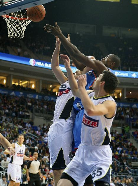 The NBA team Oklahoma City Thunder's Serge Ibaka, center, and Gasper Vidmar, left, and Emir Preldzic of  Fenerbahce Ulker fight for the ball during a basketball game in Istanbul, Turkey, Saturday, Oct