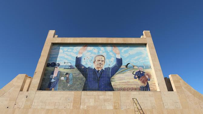 A bullet-riddled mural depicting former Syrian President Hafez al-Assad is pictured at southern entrance of the city of Hasaka