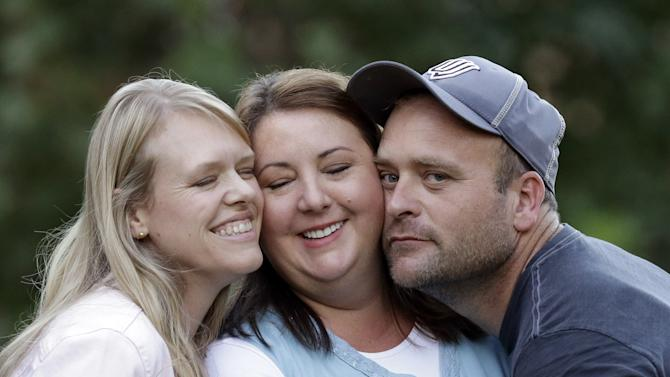 """In this Sept. 11, 2013, photo, Brady Williams poses with his wives, from left to right, Robyn and Rosemary, outside of their home in a polygamous community outside Salt Lake City. Brady Williams has five wives, 24 children but no organized religion. The latest polygamous family from Utah to open its lives to America via reality TV is a tried and true plural family. The kids range from age 2 to 20, and five are named Brady. A one-hour special called """"My Five Wives"""" is set to air Sunday on TLC offering a glimpse into the family's life. (AP Photo/Rick Bowmer)"""