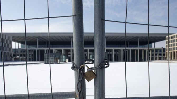 In this March 14, 2013 photo, a fence shields the main terminal of the new Berlin Brandenburg International Airport (BER) named Willy-Brandt-Flughafen in Schoenefeld near Berlin. Willy Brandt International Airport, named for Germany's famed Cold War leader, was supposed to have been up and running in late 2011, a sign of Berlin's transformation from Cold War confrontation line to world class capital of Europe's economic powerhouse. Instead it has become a symbol of how, even for this technological titan, things can go horribly wrong. After four publicly announced delays, officials acknowledged the airport won't be ready by the latest target: October 2013. To spare themselves further embarrassment, officials have refused to set a new opening date. (AP Photo/Markus Schreiber)