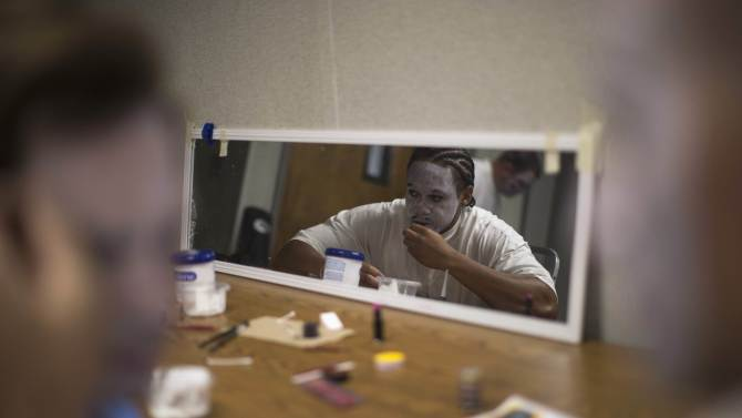 "Inmate Darreus Dale applies make-up on his face before the workshop ""Commedia Dell'Arte"", part of the The Actors' Gang Prison Project program at the California Rehabilitation Center in Norco"