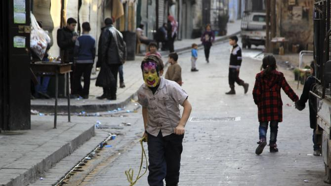 A boy wearing a mask walks along a street in the old city of Aleppo
