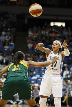 Minnesota Lynx guard Seimone Augustus (33) passes the ball over Seattle Storm guard Noelle Quinn (45) in the opening game of a first-round WNBA basketball playoff series, Friday, Sept. 20, 2013, in Minneapolis. (AP Photo/Stacy Bengs)