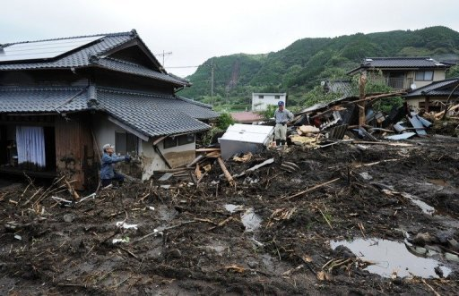<p>Workers are seen standing on the debris of a landslide after torrential rainfall in Aso City, Kumamoto prefecture, on July 17. Flood victims in Japan began a full-scale clean-up operation after record rainfall forced hundreds of thousands to flee and left at least 32 dead or missing.</p>