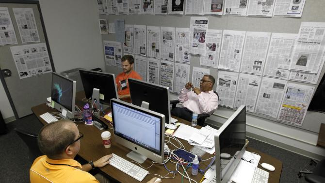 News curator James Karst, background left, director of print Terry Baquet, center, and production systems manager Stephen Barrouquere, bottom left, work amongst hanging prototypes of the New Orleans Times-Picayune's upcoming three-day-a-week newspaper at the paper's offices in New Orleans, Thursday, Sept. 27, 2012.  As The Times-Picayune scales back its print edition to three days a week, the Baton Rouge newspaper is starting its own daily edition to try to fill the void. The move by The Advocate sets up an old-fashioned newspaper competition, even as more and more people get their news online and from cellphones. (AP Photo/Gerald Herbert)