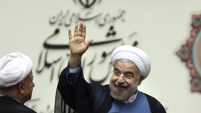 "Iran's new President Hasan Rouhani, waves after swearing in at the parliament, in Tehran, Iran, Sunday, Aug. 4, 2013. Iran's new president on Sunday called on the West to abandon the ""language of sanctions"" in dealing with his country over its contentious nuclear program, hoping to ease the economic pressures now grinding its people. Rouhani spoke after being sworn in as president in an open session of parliament Sunday, capping a weekend that saw him endorsed by Ayatollah Ali Khamenei, Iran's supreme leader. (AP Photo/Ebrahim Noroozi)"